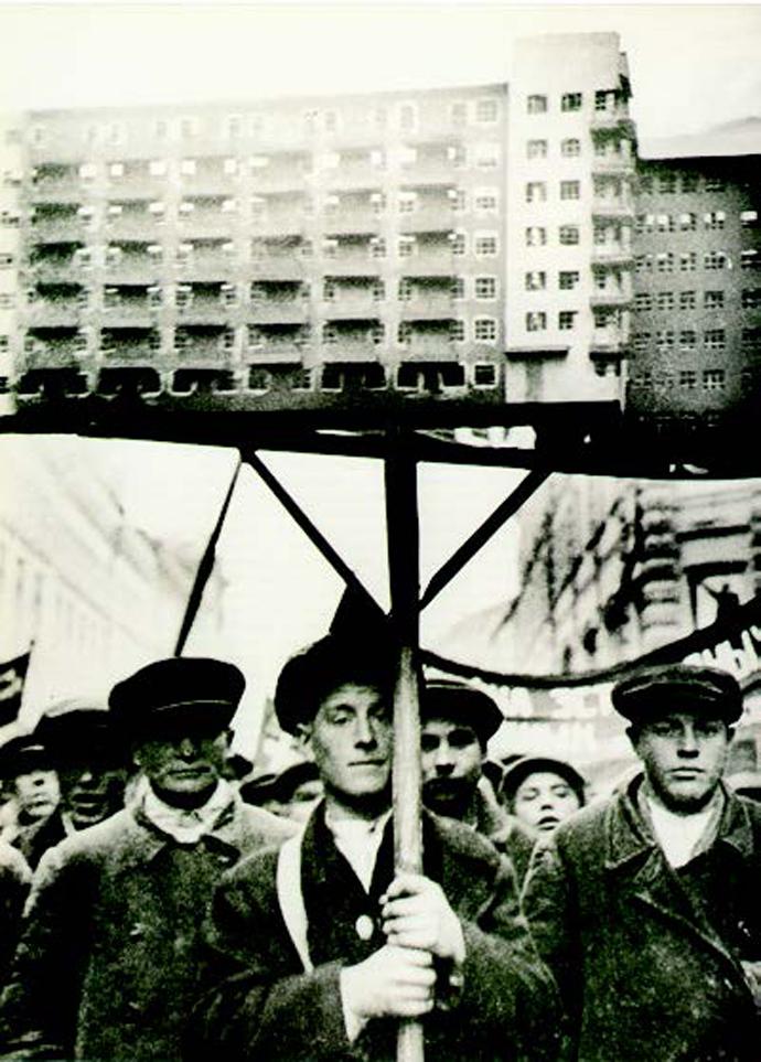 Trabajadores de la construcción de la Unión Soviética desfilando con modelos de casas modernistas montadas en pértigas. 1931.