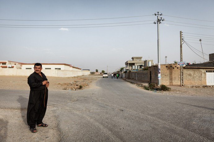 Daratoo, Kurdistan, Northern Iraq. A man stands at a wide crossroad in the collective town of Daratoo. Photo: Leo Novel